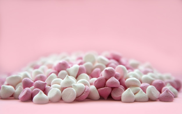 Pink and white mini meringues in the shape of drops, which lie on a pink surface.