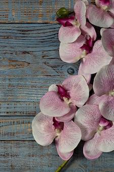青い木製の背景にピンクの白い蘭の花