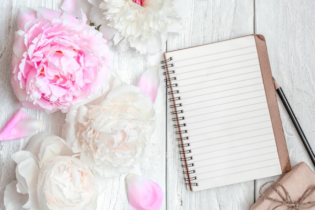 Pink and white peony flowers with blank lined notebook and gift box on white wooden table