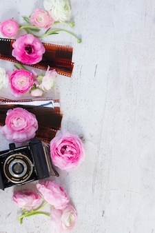 Pink and white ranunculus flowers with retro camera flat lay scene