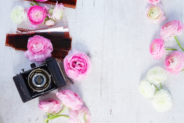 Pink and white ranunculus fresh blooming flowers with retro camera flat lay scene, copy space on wooden desktop