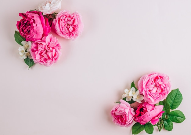 Pink and white roses on beige background top view flat lay frame or wreath