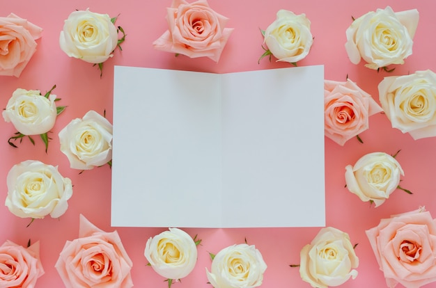 Pink and white roses put on pink background with empty white card for san valentine's day