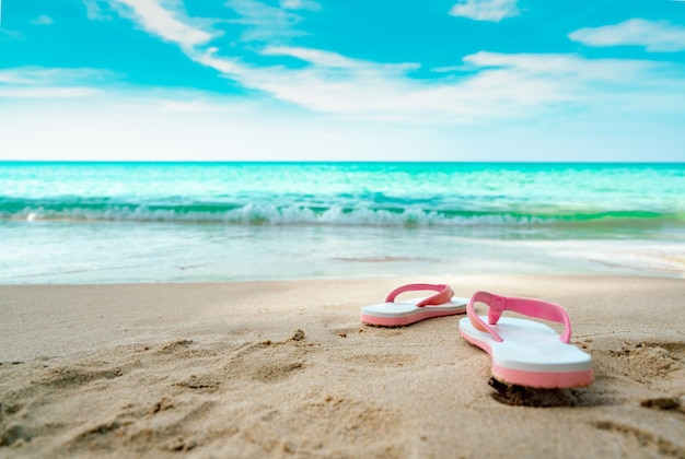 Pink and white sandals on sand beach. casual style flipflop were removed at seaside. summer vacation on tropical beach.