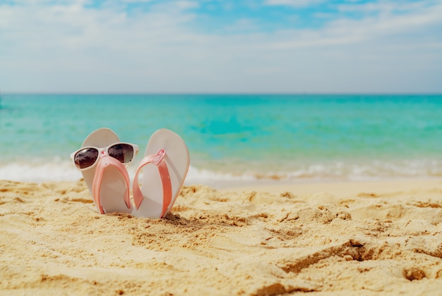 Pink and white sandals, sunglasses on sand beach at seaside. casual fashion style flipflop and glasses at seashore. summer vacation on tropical beach. fun holiday travel on sandy beach.