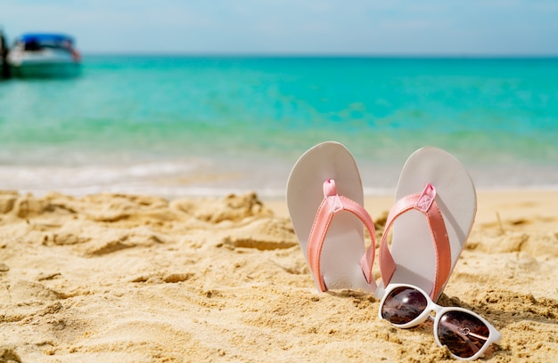 Pink and white sandals, sunglasses on sand beach at seaside. casual fashion style flipflop and glasses at seashore. summer vacation on tropical beach.
