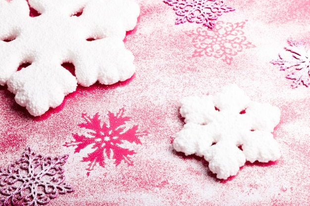 Pink and white snowflakes on a pink background. christmas background. top view. copyspace. decorative snow.