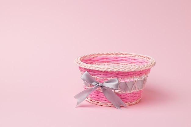 淡いピンクの表面にピンクの籐のバスケット