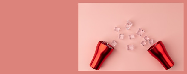 Pink wide background with a red cup and ice on the floor