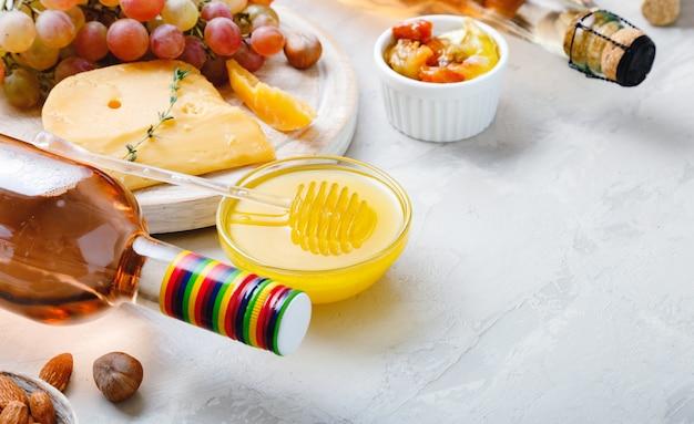 복사 공간이 있는 밝은 회색 소박한 콘크리트 배경에 핑크 와인 구성. 로즈 와인 병 치즈 견과류와 핑크 포도, 꿀. 카망베르 치즈, 와인 바 스낵.