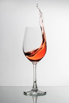 Pink wine splashing up the side of a wineglass