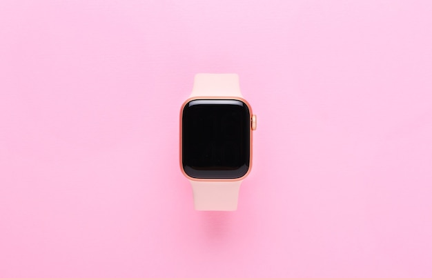 Pink woman smart watch on pink background.