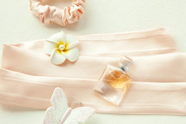 분홍색 배경에 아름다운 병과 흰색 꽃에 있는 분홍색 여성용 향수. 실크 핑크 둥근 머리띠 흰색 절연입니다. 플랫 레이 미용 도구 및 액세서리 헤어 스크런치, 헤어 밴드,