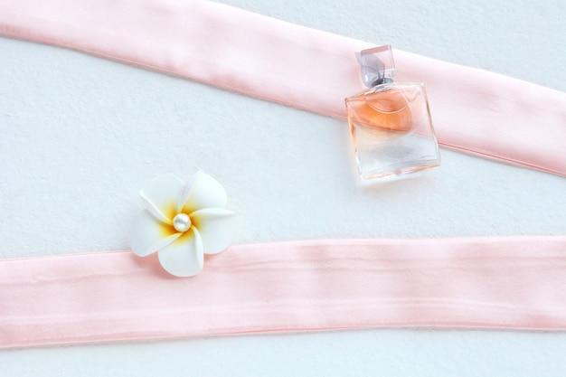 아름다운 병에 든 분홍색 여성용 향수와 분홍색 배경에 흰색 꽃