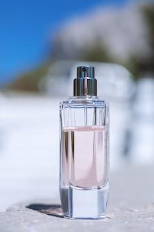 Розовый женский парфюм на синем