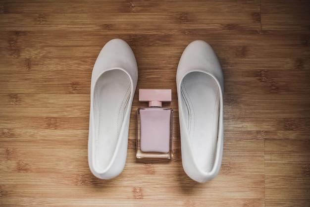 Розовые женские духи между двумя белыми туфлями
