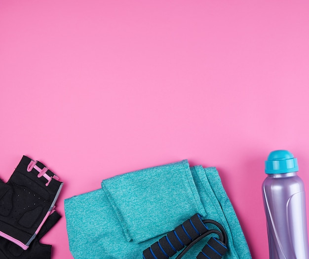 Pink women's sneakers, bottle of water, gloves and a jump rope for sports on a pink surface