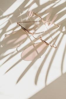 花の影と白いテーブルの上のピンクの女性のサングラス