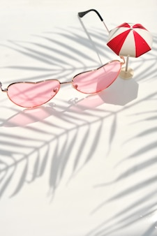 Pink women's sunglasses on white water background with floral palm shadow and toy umbrella. minimal fashion lifestyle background.
