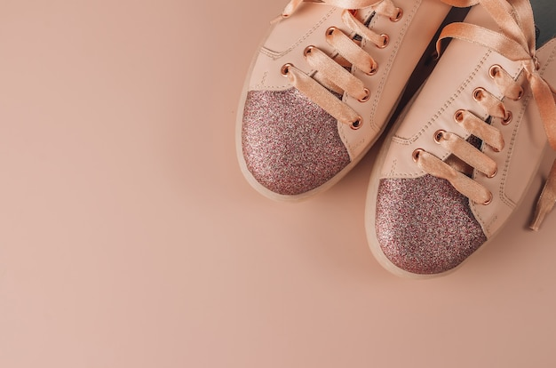 Pink women sneakers on a pink background. flat lay of modern shoes.