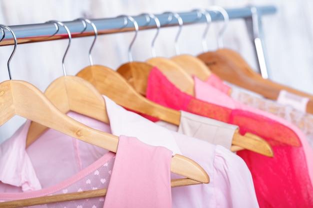 패션 매장의 선반에 나무 옷걸이에 분홍색 여자 옷. . 옷장 여성 드레스, 블라우스 클로즈업