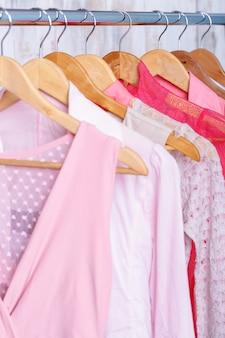 패션 매장의 선반에 나무 옷걸이에 분홍색 여자 옷. 옷장 여성 드레스, 블라우스
