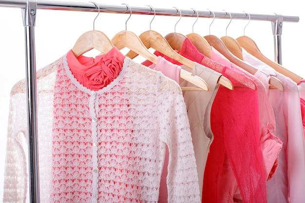 Розовая женская одежда на деревянных вешалках на стойке на белом фоне. гардеробные женские платья, блузки