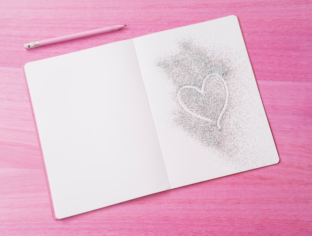 Pink wooden background with glitter notepad and heart