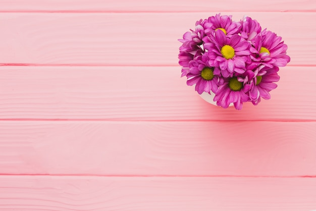 Pink wooden background with purple flowers