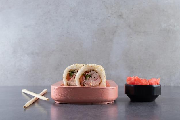 Tavola di legno rosa di delizioso rotolo di sushi posto su sfondo di pietra.
