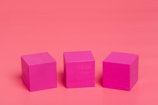 ピンク色の背景にピンクの木製キューブ Premium写真