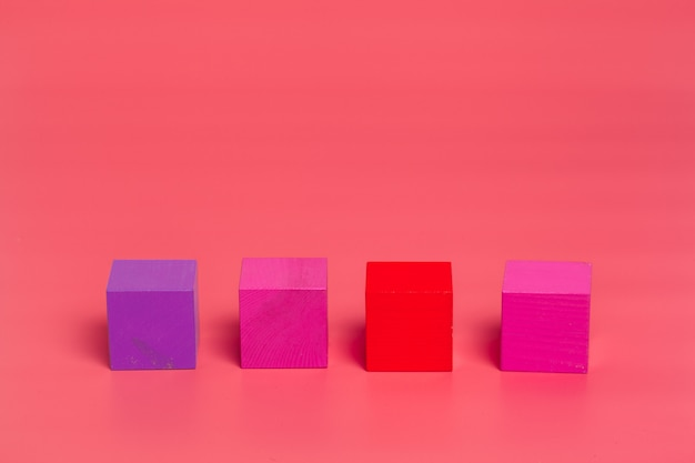 Pink wooden cubes on pink colored background