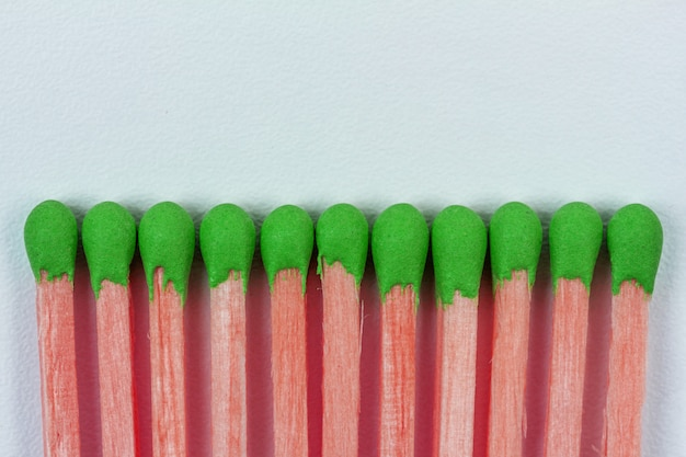 Pink wooden matches with green sulphur on grey