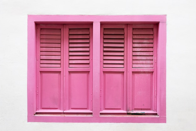 Pink wooden window is classic vintage style on white cement wall background.