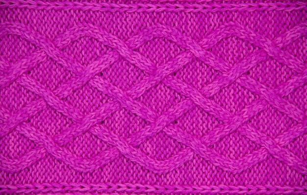 Розовая шерстяная пряжа вязаная фактура. вязаная вручную 12 петелька из тесьмы. по горизонтали. крупным планом