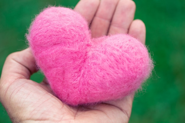 緑の自然の背景に手に横たわってピンクの羊毛の心