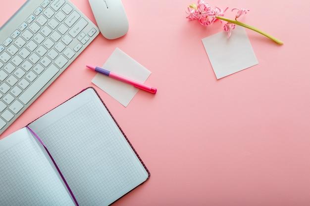 핑크색 업무용 책상. 작업 공간 컴퓨터 키보드와 마우스 메모장 편지지가 있는 사무실 테이블. 분홍색 배경에 복사 공간이 있는 상위 뷰 사무실 테이블 책상. 플랫 레이
