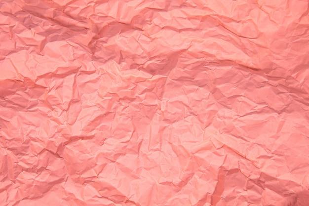 ピンクのしわは、紙のページのテクスチャの粗い背景で古いしわくちゃになりました。しわグランジ羊皮紙パターンヴィンテージ