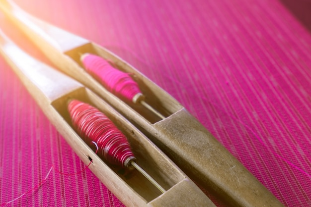 Pink yarn in weaving shuttle tool on traditional handmade fabric. textile weaving. weaving using traditional weaving loom and shuttle.
