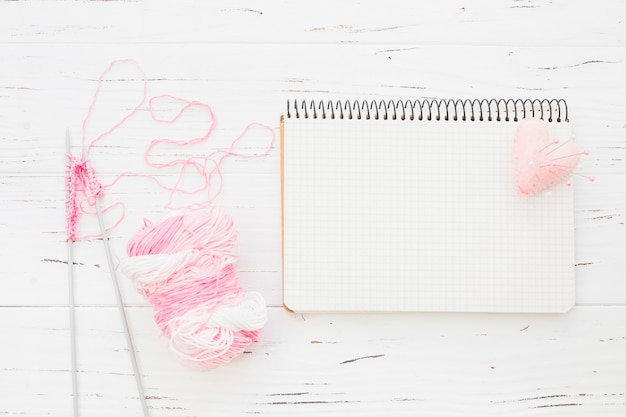 Pink yarn with crochet beside notepad and heart on wooden background