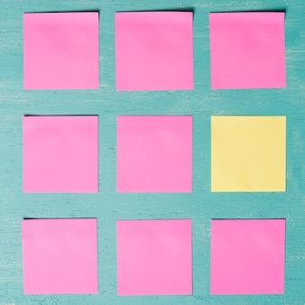 Pink and yellow adhesive notes on wooden textured background