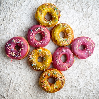 Pink and yellow doughnuts top view on a white textured background