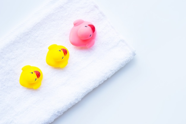 Pink and yellow duck  toys on white towel.