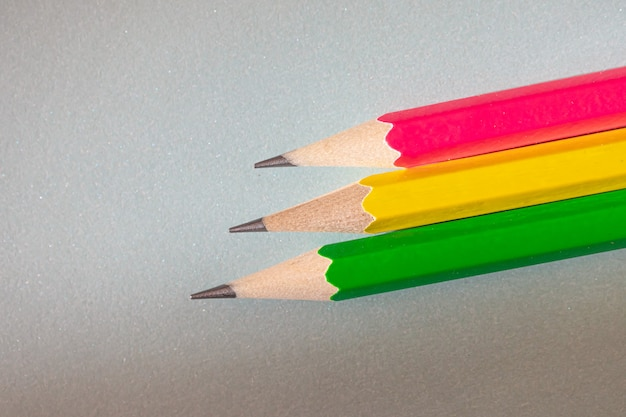Pink, yellow and green graphite pencils on gray