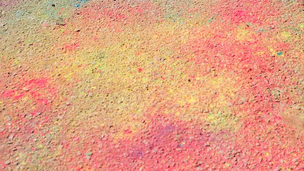 Pink and yellow holi color on ground