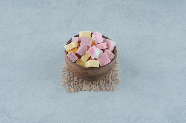 Caramelle di marshmallow rosa e gialle in una ciotola di legno su superficie bianca