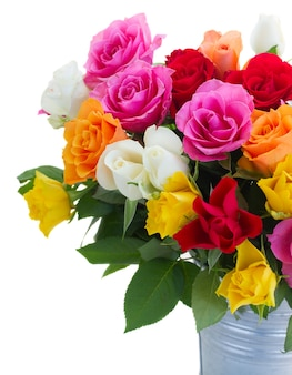 ピンク、黄色、オレンジ、赤の新鮮なバラの金属製の鍋のクローズアップ、白で隔離