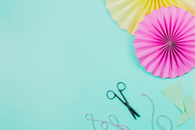 Ventilatori di carta rosa e giallo con forbice e filo sullo sfondo verde acqua