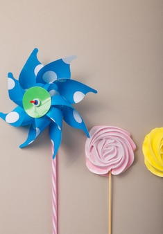 Pink, yellow rose candy  with colorful toy windmills in pastel colors on a wooden stick on a grey  background, valentine, mother's day.