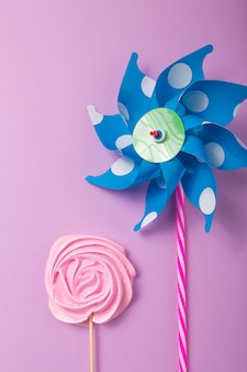Pink, yellow rose candy  with colorful toy windmills in pastel colors on a wooden stick on a grey  background